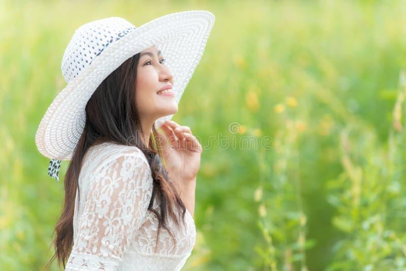 Forma de vida asiática feliz de la mujer en la salida del sol de la flor del amarillo del prado Al aire libre activos se relajan  fotos de archivo libres de regalías