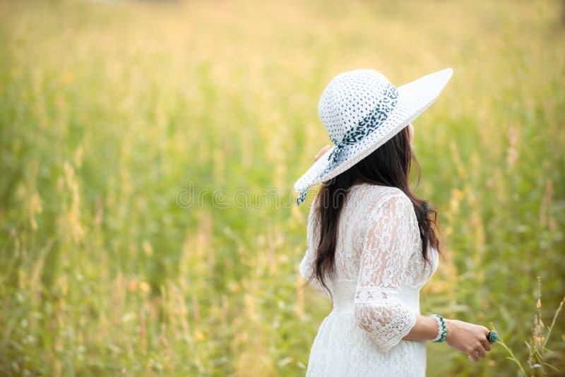 Forma de vida asiática feliz de la mujer en la salida del sol de la flor del amarillo del prado Al aire libre activos se relajan  imagenes de archivo