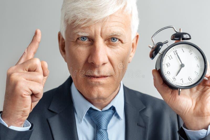 Forma de vida del negocio Situación del hombre de negocios aislada en tiempo que muestra gris en el despertador que señala encima fotografía de archivo libre de regalías