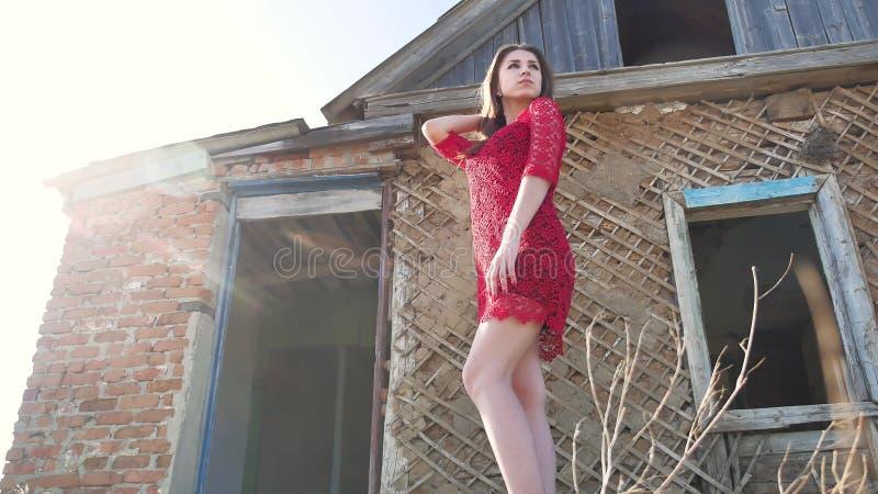 Forma de vida hermosa de la muchacha en un vestido rojo La muchacha atractiva en un vestido se está colocando al lado de la casa  imagen de archivo libre de regalías