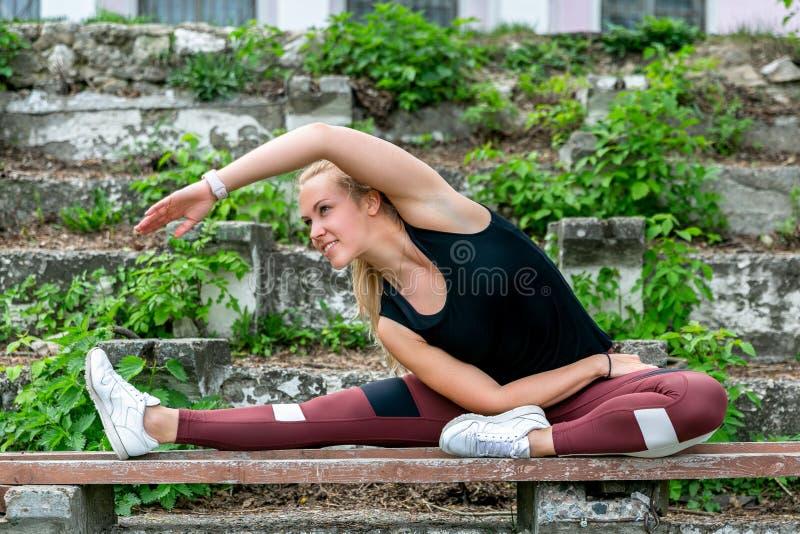 Forma de vida de la aptitud Mujer joven que calienta en el banco antes de ejercicios que hacen de entrenamiento para estirar sus  imagen de archivo