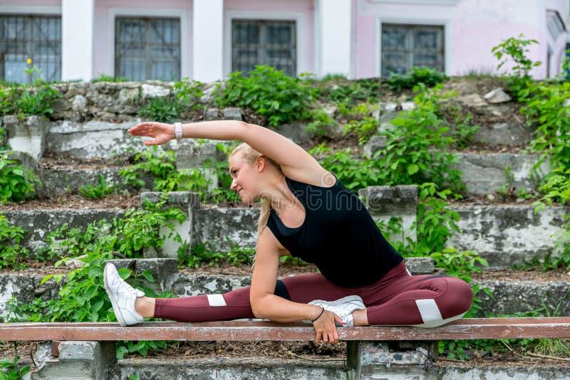 Forma de vida de la aptitud Mujer joven que calienta en el banco antes de ejercicios que hacen de entrenamiento para estirar sus  fotos de archivo libres de regalías
