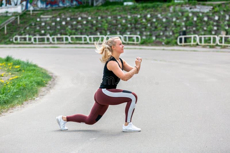 Forma de vida de la aptitud Mujer joven que hace estocadas en un salto Entrenamiento en el estadio Concepto sano de la vida imágenes de archivo libres de regalías