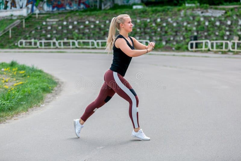 Forma de vida de la aptitud Mujer joven que hace estocadas en un salto Entrenamiento en el estadio Concepto sano de la vida imagenes de archivo