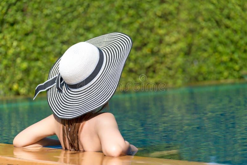 Forma de vida de la mujer joven tan feliz en el sombrero grande que se relaja en el lujo de la piscina imagen de archivo