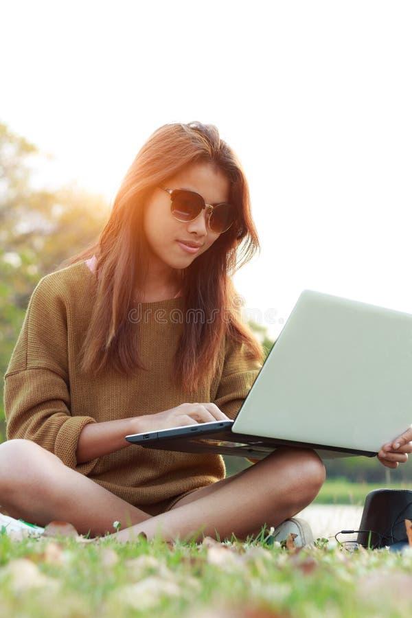 Forma de vida moderna al aire libre del ordenador portátil del ordenador portátil del uso de la sonrisa de la muchacha fotografía de archivo libre de regalías