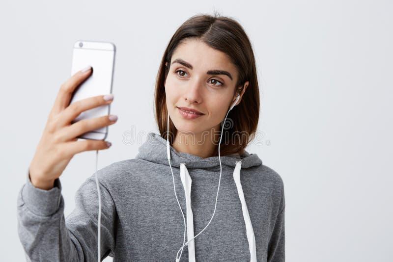 Forma de vida moderna Ciérrese para arriba de la muchacha caucásica morena joven hermosa en sudadera con capucha casual que habla imagenes de archivo