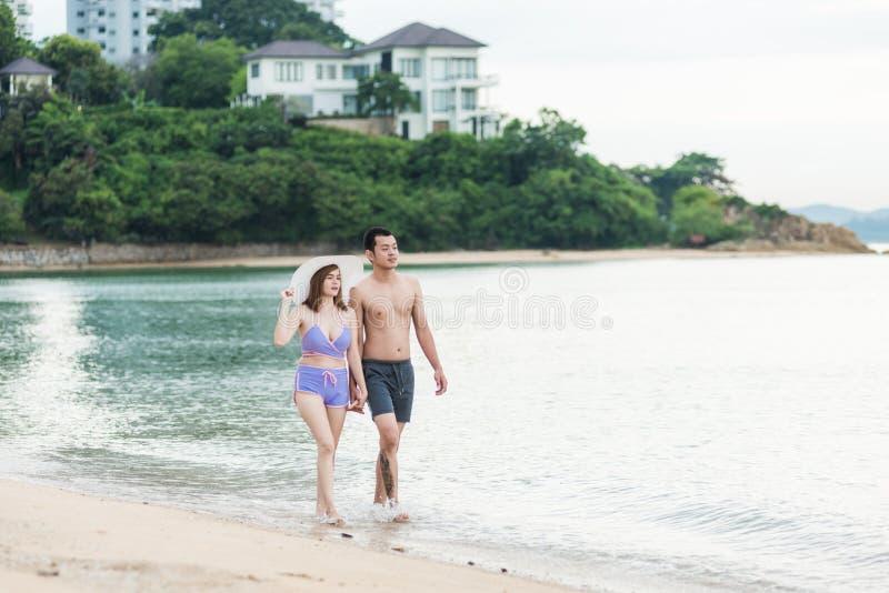 Forma de vida romántica de los pares jovenes felices que camina en la playa tropical imágenes de archivo libres de regalías