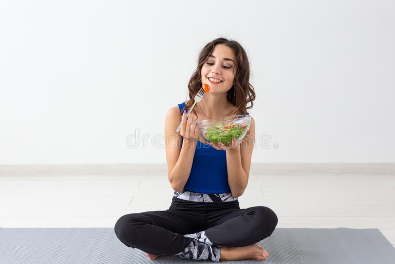 Forma de vida sana, gente y concepto del deporte - mujer de la yoga con un cuenco de ensalada vegetal foto de archivo libre de regalías