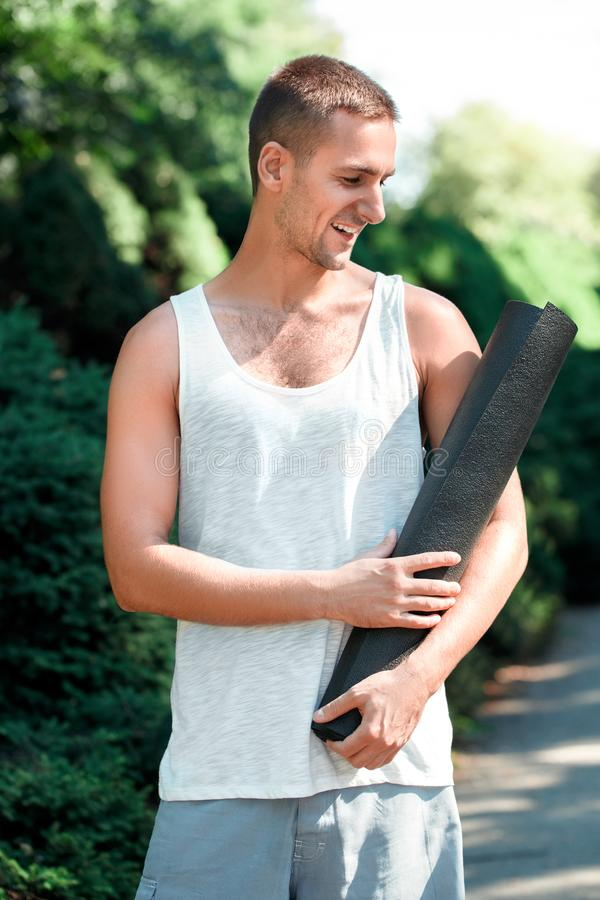 Forma de vida sana Situación practicante del aire libre de la yoga del hombre que mira la estera alegre imagen de archivo libre de regalías