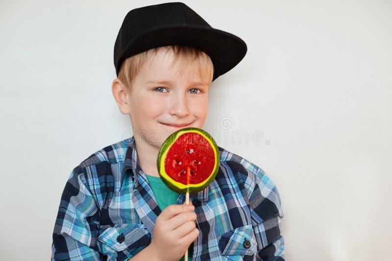 Forma de vida y concepto de la gente Pequeño niño masculino adorable con los ojos azules y el pelo justo en casquillo negro y la  foto de archivo