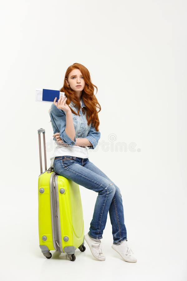 Forma de vida y concepto del viaje: La mujer caucásica hermosa joven se está sentando en suitecase y está esperando su vuelo imagen de archivo libre de regalías