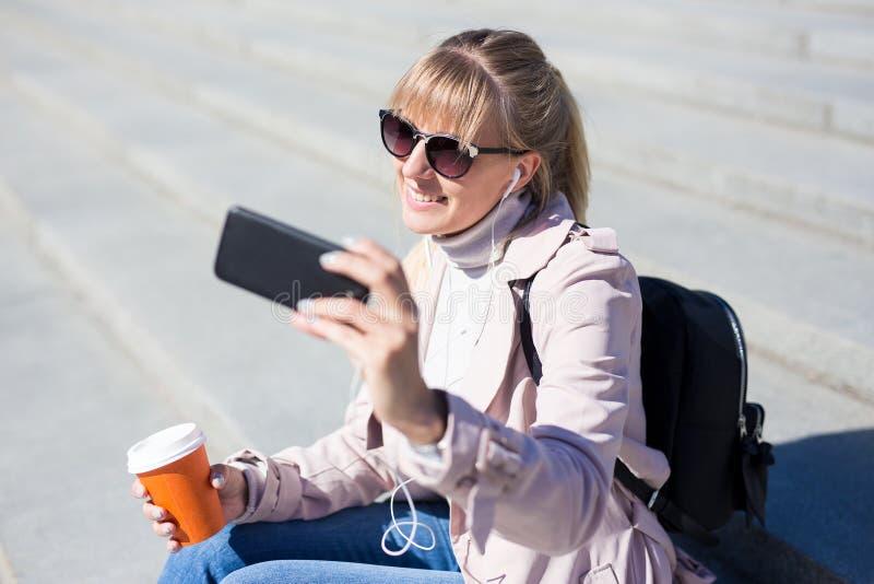 Forma de vida y concepto del viaje - mujer joven que se sienta en las escaleras y que toma la foto del selfie con smartphone fotos de archivo