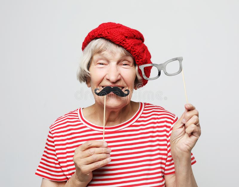 Forma de vida y concepto de la gente: la abuela divertida con el bigote y los vidrios falsos, ríe y se prepara para el partido fotos de archivo