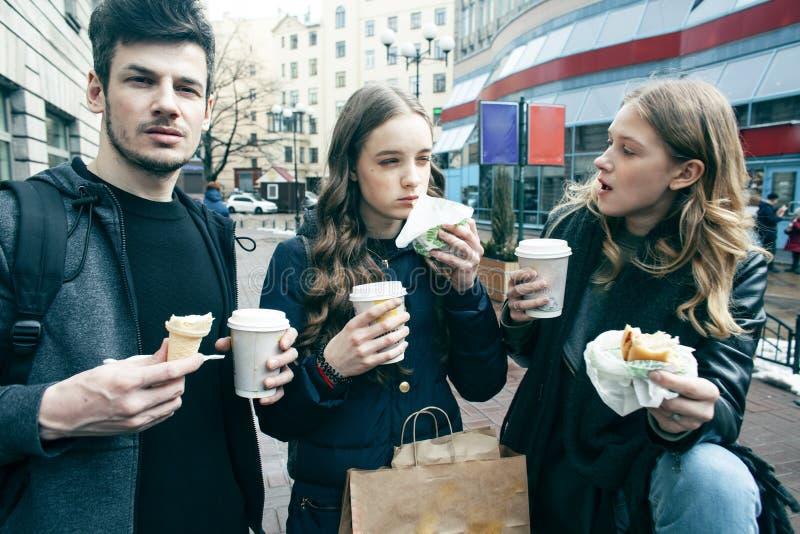 Forma de vida y concepto de la gente: dos muchachas e individuo que comen los alimentos de preparaci?n r?pida en la calle de la c fotos de archivo