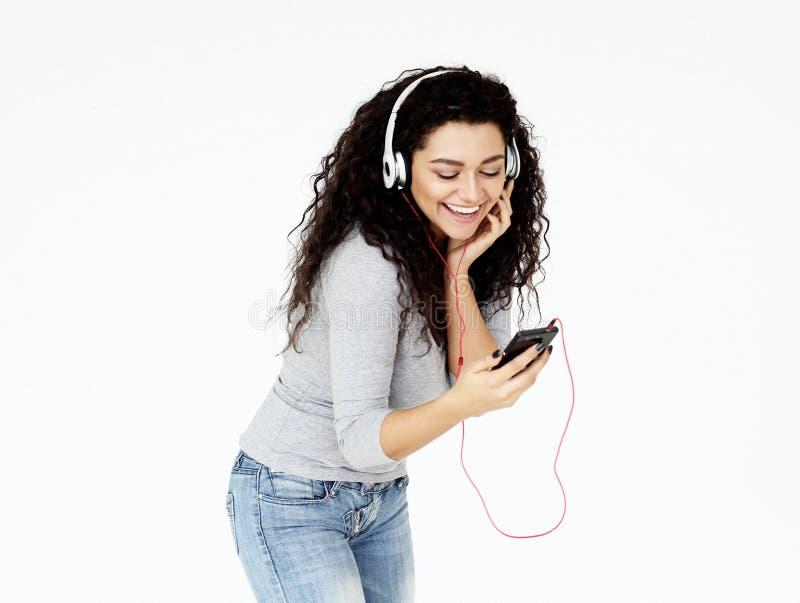 Forma de vida y concepto de la gente: Mujer joven hermosa en auriculares que escucha la música que se coloca en el fondo blanco imagen de archivo libre de regalías