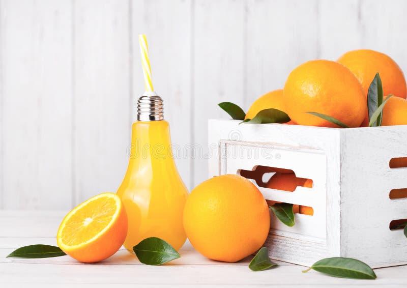 Forma de vidro da lâmpada do suco de laranja fresco orgânico fotografia de stock