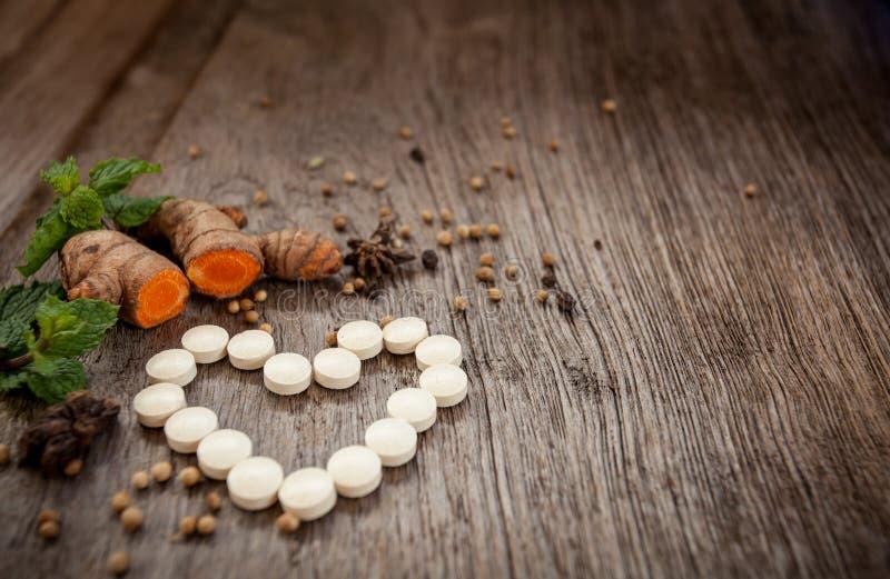 Forma del corazón de la hierba de la medicina, píldoras herbarias con medicinal sano foto de archivo