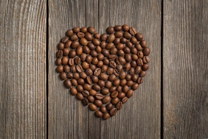 Forma del corazón hecha de los granos de café en la tabla de madera imagen de archivo libre de regalías