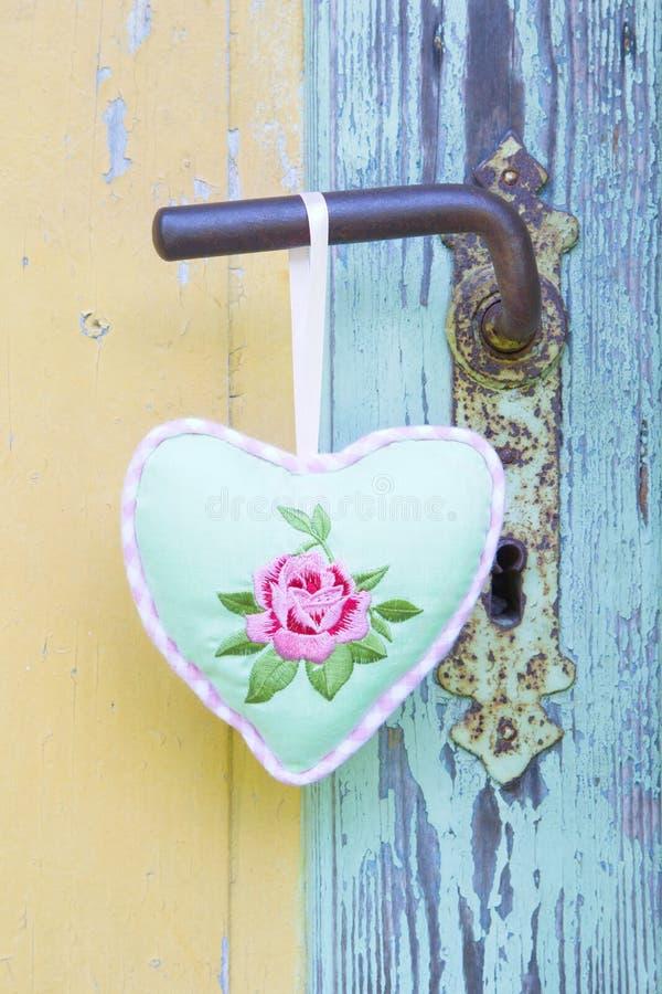 Forma del cuore che appende sulla maniglia di porta arrugginita per il biglietto di S. Valentino, christma immagini stock libere da diritti