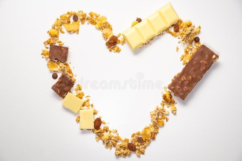 Forma del cuore da granola, muesli con la banana secca, altri frutti e cioccolato al latte bianco Vista superiore Dieta sana ed e immagine stock