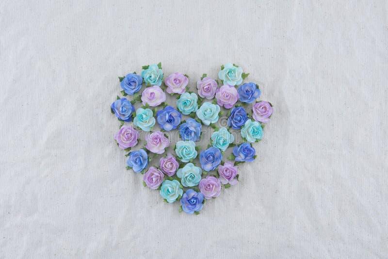 Forma del cuore fatta dai fiori di carta della rosa blu di tono immagine stock