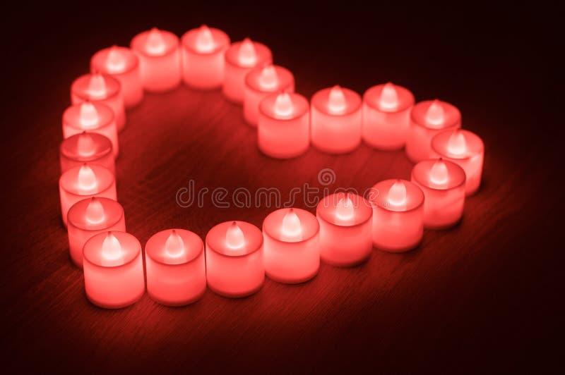 Forma del cuore fatta dalle candele principali rosse fotografia stock