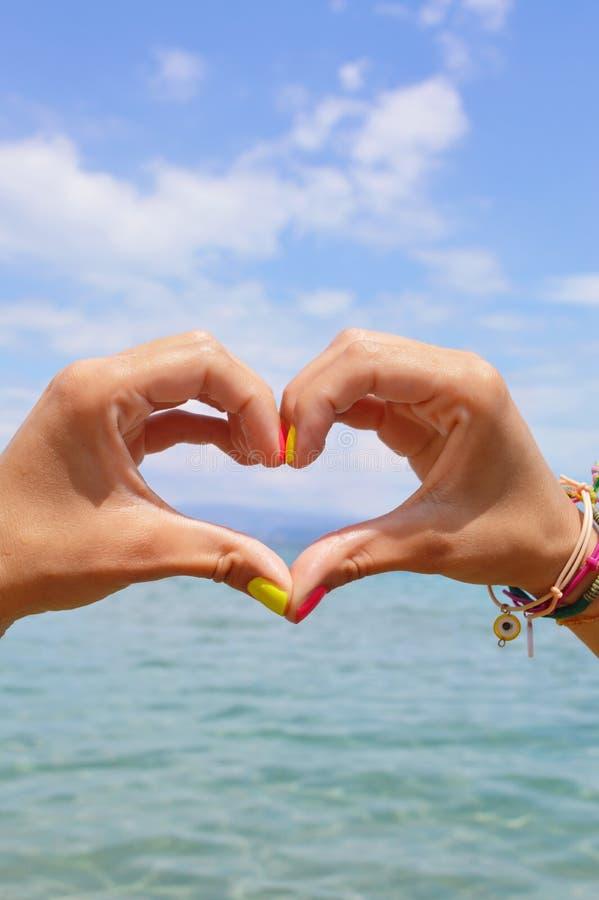 Forma del cuore fatta delle mani contro il mare ed il cielo fotografie stock libere da diritti