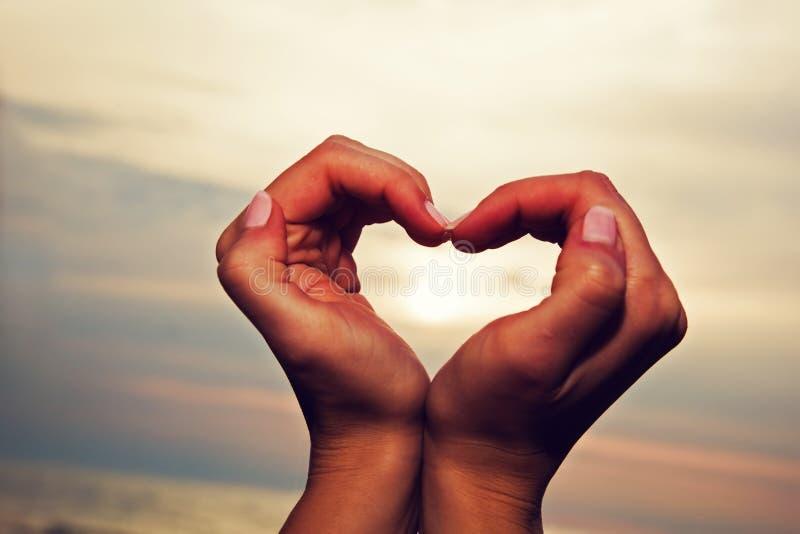 Forma del cuore in mani della donna al tramonto fotografia stock libera da diritti