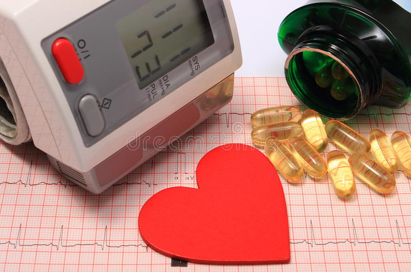 Forma del cuore, monitor di pressione sanguigna e compresse sull'elettrocardiogramma immagine stock libera da diritti