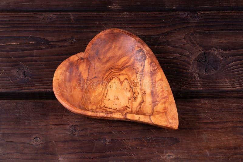 Forma del cuore del piatto su un fondo di legno, scuro, fatto a mano, rustico fotografia stock libera da diritti