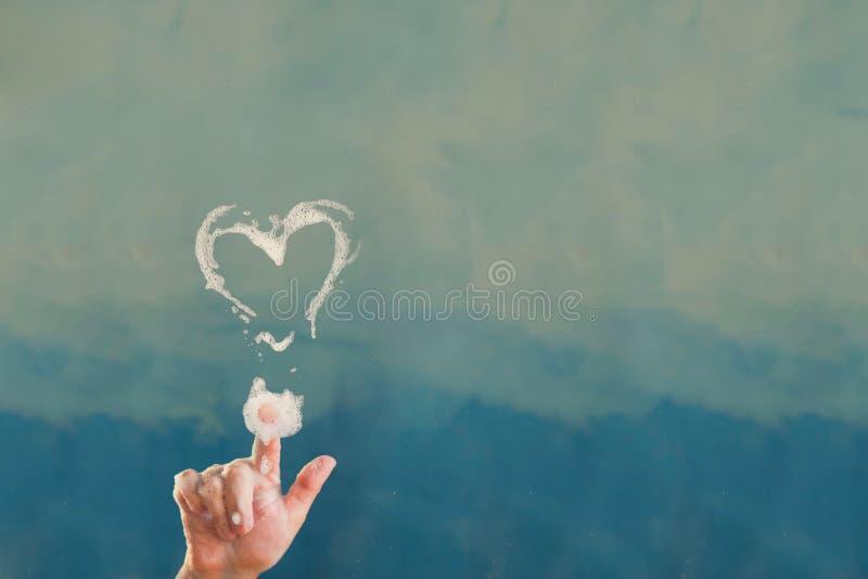 Forma del cuore del sapone sulla porta di vetro trasparente fotografie stock