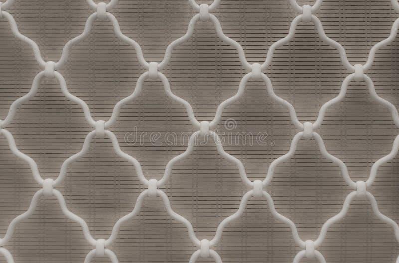 Forma del diamante del acero curvado blanco en la ventana del enrejado, fondo gris de cortina de bambú, enrejado del hierro labra foto de archivo libre de regalías