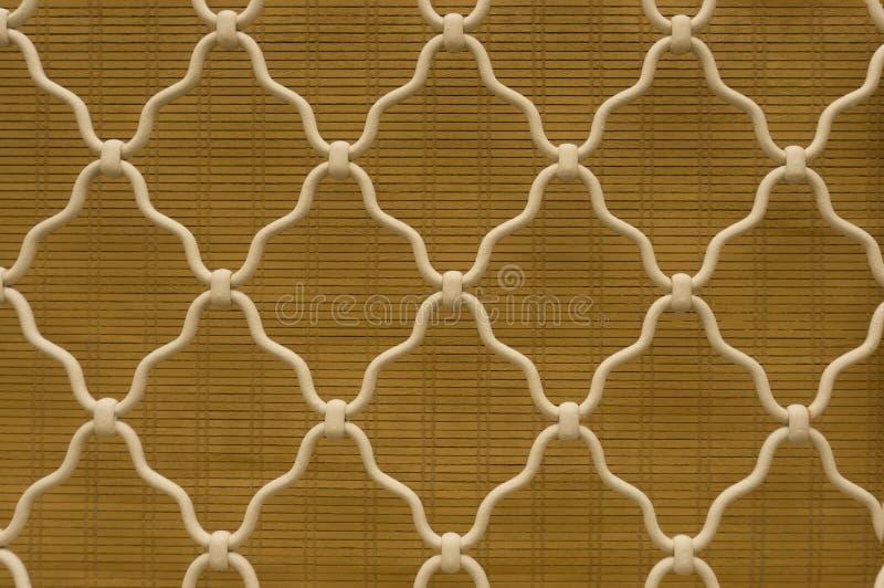 Forma del diamante del acero curvado blanco en la ventana del enrejado, fondo marrón de cortina de bambú, enrejado del hierro lab fotos de archivo libres de regalías