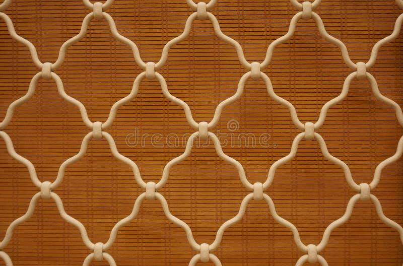 Forma del diamante del acero curvado blanco en la ventana del enrejado, fondo marrón de cortina de bambú, enrejado del hierro lab fotografía de archivo libre de regalías