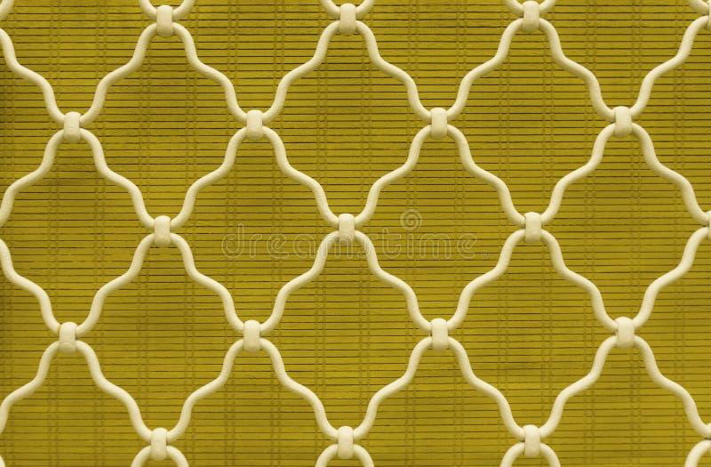 Forma del diamante dell'acciaio curvo bianco sulla finestra della grata, fondo giallo della tenda di bambù, grata d'annata del fe immagini stock libere da diritti