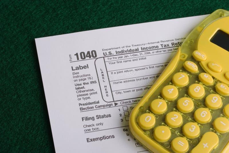 Forma del impuesto sobre la renta con la calculadora imágenes de archivo libres de regalías