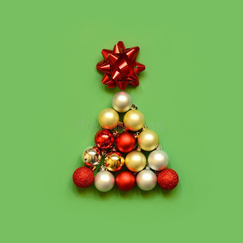 Forma dell'albero di Natale creata con bauble su sfondo verde fotografie stock libere da diritti