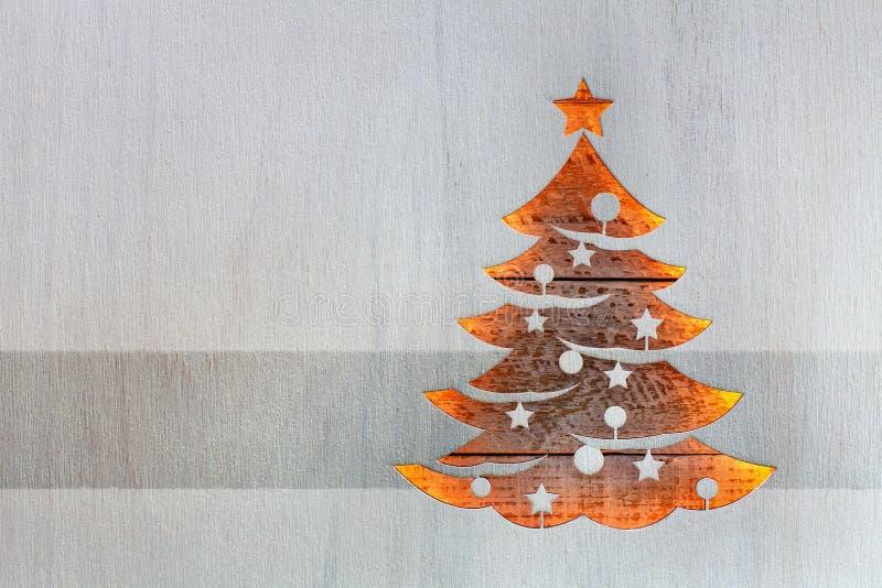 Forma dell'albero di Natale nel bordo di legno che lascia attraverso le luci calde fotografia stock