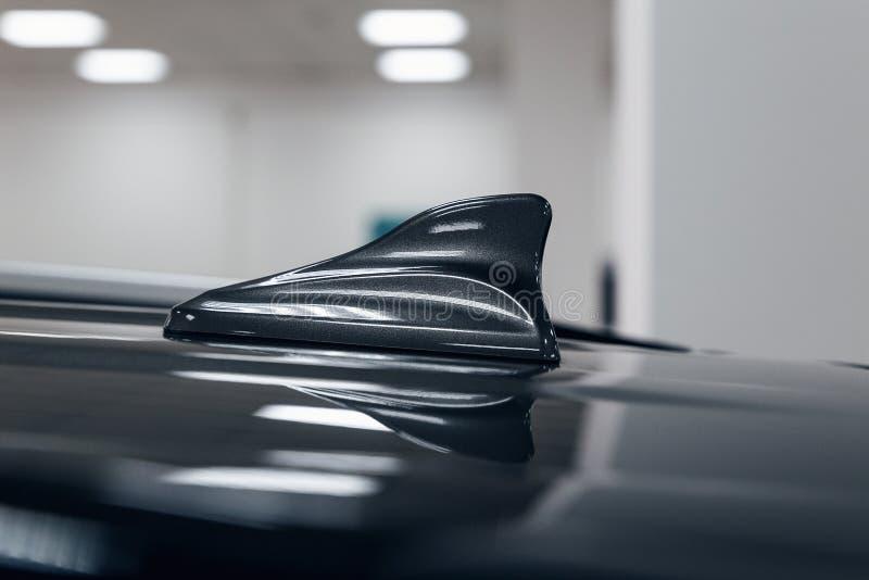 Forma dell'aletta dello squalo dell'antenna di GPS del primo piano su un tetto dell'automobile per la radio fotografia stock