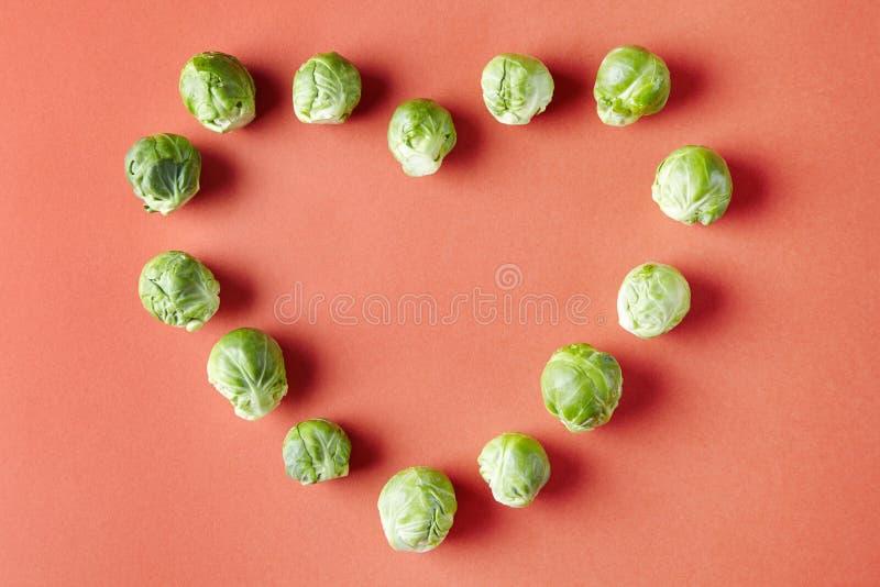 Forma di amore del cuore dei cavoletti di Bruxelles su fondo rosso Verdure stagionali nel modello moderno di stile fotografia stock libera da diritti