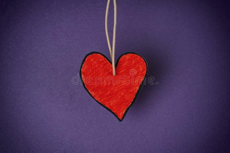 Forma di carta rossa del cuore contro fondo porpora fotografia stock libera da diritti