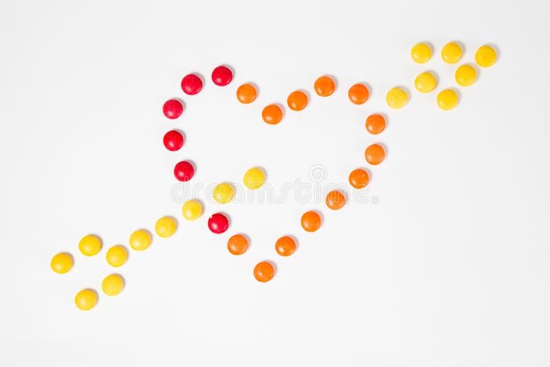 Forma di cuore penetrante con la freccia - simbolo di amore - fatta dalle caramelle dolci variopinte immagini stock