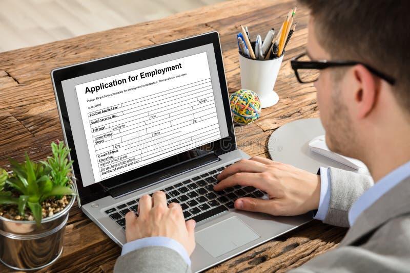 Forma di occupazione di Filling Application For dell'uomo d'affari sul computer portatile fotografie stock libere da diritti