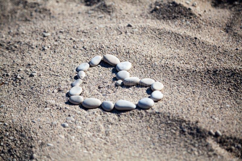 Forma di pietra del cuore sulla sabbia della spiaggia di estate immagine stock libera da diritti
