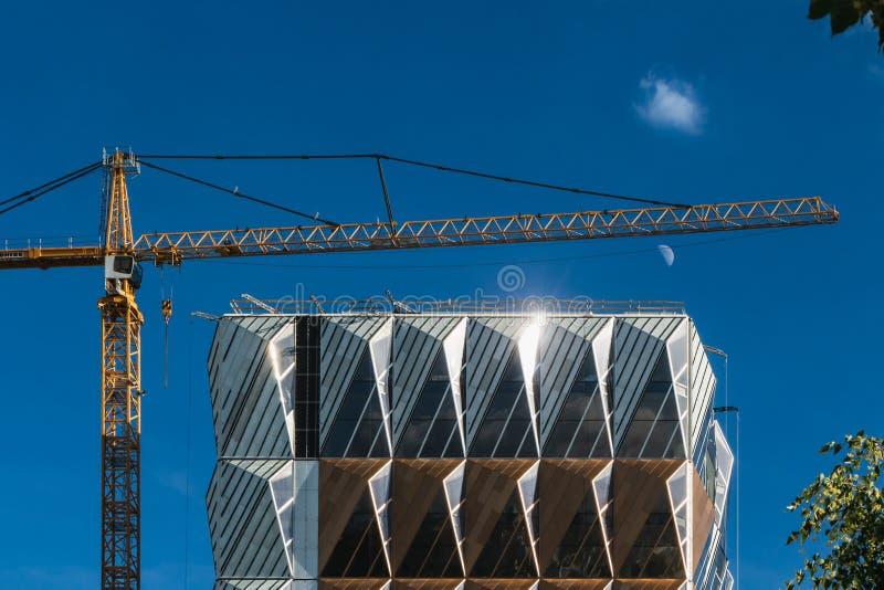 Forma di spazio insolita di costruzione moderna con una gru di costruzione gialla contro un cielo blu con la luna e una nuvola bi immagine stock libera da diritti