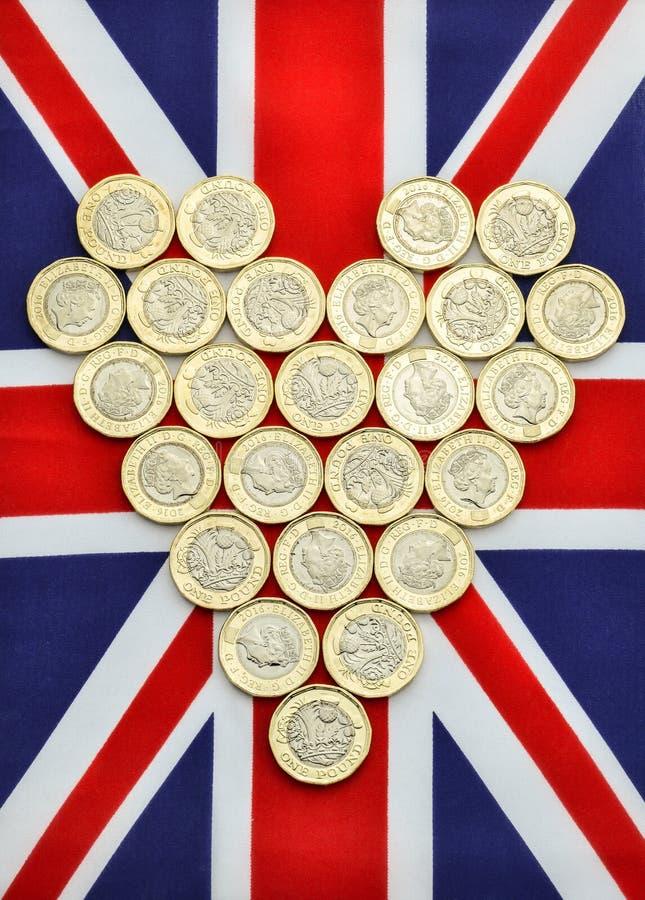 Forma do coração de moedas de libra novas na bandeira britânica foto de stock