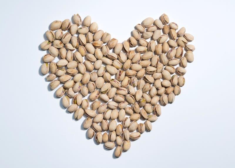 A forma do coração estilizou de porcas de pistaches no fundo branco com espaço para o tipo Fundo da mistura do alimento, vista su imagem de stock