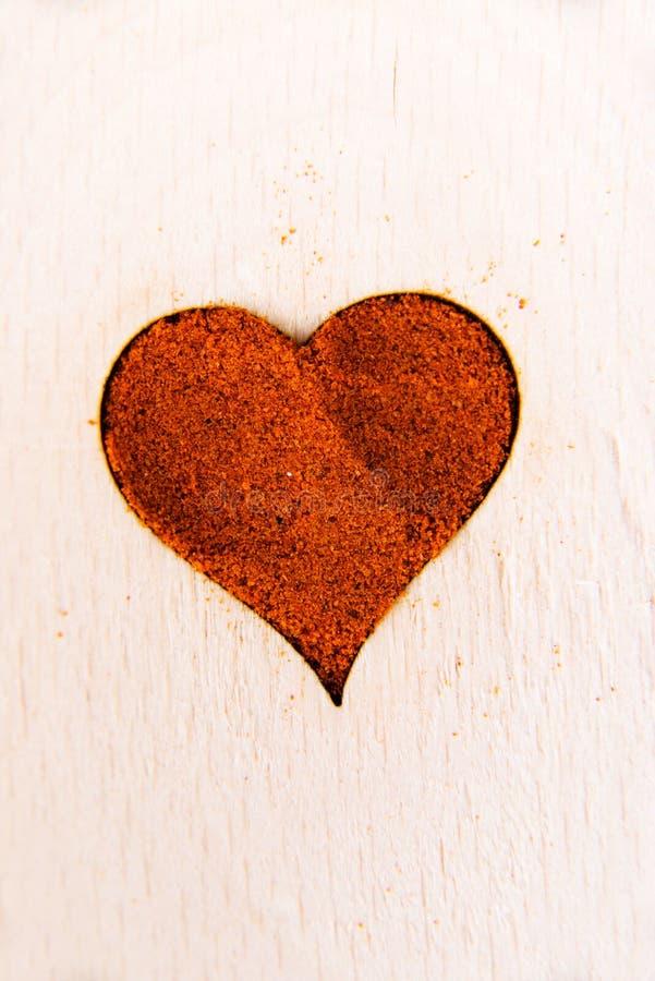 Forma do coração feita da especiaria em uma colher de madeira. fotografia de stock