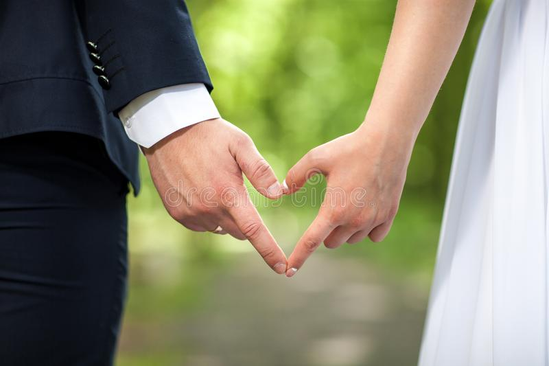 Forma do coração feita das mãos fêmeas e masculinas junto os amantes acoplam a fatura de um coração com mãos no fundo verde fotos de stock